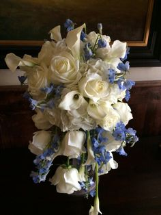cascade bouquet with blue delphinium, white hydrangea , calla lilies and roses