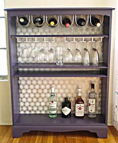 Find an inexpensive bookshelf at your local Goodwill and paint it any color you like and then if you like add a fun background with wrapping paper or scrapbook paper if you want a more fun look. Just add wine and glass hooks to hang your bottles and glasses! It's that easy and it makes for a great entertaining space!