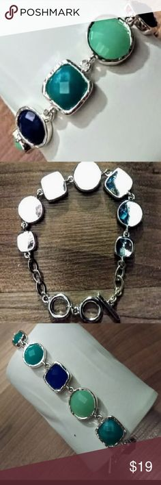 Jeweled Bracelet, silvertone setting, no lue NWOT Bracelet set in Silvertone with jewel-toned blue, turquoise, green faux gemstones. Tootle closure with 2 rings for sizing. Gift box upon request. EUC New, never worn, bought at Dillard's. Jewelry Bracelets