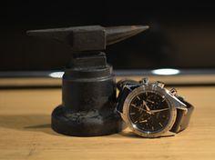 Steel on steel. Omega Speedmaster '57 vintage style next to a goldsmith anvil.