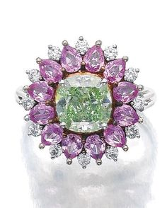 FANCY INTENSE YELLOWISH GREEN DIAMOND, PINK SAPPHIRE AND DIAMOND RING. Claw-set with a cushion-shaped fancy intense yellowish green diamond weighing 2.83 carats within a frame of pear-shaped pink sapphires and brilliant-cut diamonds, size 531/2, partial French assay and maker's marks.