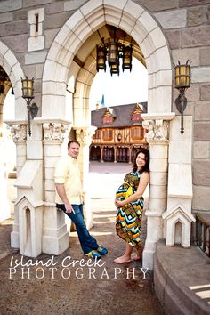 Couple poses for maternity portraits next to great disney world architecture