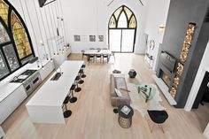 Is it a cathedral or a kitchen? A crisply modern aesthetic pairs with sky-high ceilings and arched stained glass windows in this incredible room that includes a kitchen, dining and lounge area.