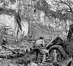 Wary riflemen of the 5th Marines advance through a devastated Japanese bivouac area to the northeast of the Peleliu airfield. The concealed enemy troops took full advantage of the rocky terrain, forcing the Marines to clear out each nook and cranny. Department of Defense Photo (USMC) 96763