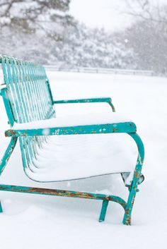 Rusty Aqua turquoise blue metal park bench in the snow