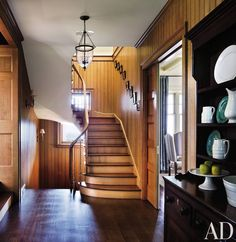 The floor, stairs, and beadboard paneling in the hall of a Ferguson & Shamamian Architects–designed home on Martha's Vineyard, Massachusetts, are made of carefully selected American white oak. The single-arm sconces are from Circa Lighting.  ARCHITECT: Ferguson & Shamamian Architects DESIGNER: Victoria Hagan Interiors PHOTOGRAPHER: Scott Frances
