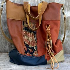 One of a kind, handmade, leather tote made with hand-sewn leather patches and antique carpet. The antique carpet was part of a Persian rug and is worn and faded. The bag is in a variety of soft leathers in chestnut, saddle brown, navy, sage, russet, burgundy, and olive. The patchwork is