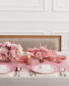 """Stick to a less-is-more approach, and your pinks will really pop. Here, a neutral backdrop provides the canvas for a striking tablescape, complete with luxe velvet runner, gilded votives, sparkling rosé, and bunches of densely clustered dahlias, garden roses, andromeda, and protea.The Details: """"Louis"""" sofa from Bridge,Missoni """"Margherita"""" dinner plates from Bloomingdales,Mood Fabrics home velvet #7173, andJayson Home tea-light holders."""