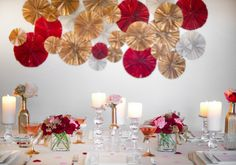 gold, red and silver paper wall decor, tapered glass candlesticks and pink and red roses