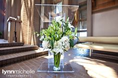 modern white wedding, beautiful white and green floral arrangement, clear podium.