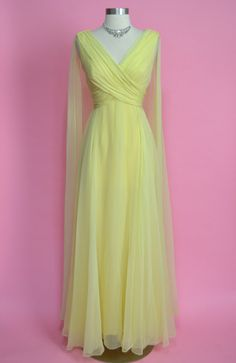 THE DETAILS: - light yellow nylon chiffon - metal zipper in the back - draping across the bust - shoulder scarfs on both of the shoulders that