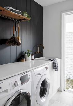 The laundry space of this chic beach house in Mooloolaba leads towards the rear of the property and features black panels, white cabinetry, and a timber floating shelf. White Laundry Rooms, Modern Laundry Rooms, Laundry In Bathroom, Laundry In Kitchen, Laundry Room Shelves, Laundry Room Remodel, Laundry Room Organization, Laundry Nook, Laundry Cabinets