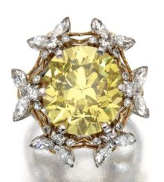 PLATINUM, 18 KARAT GOLD, FANCY VIVID YELLOW DIAMOND AND NEAR COLORLESS DIAMOND RING, SCHLUMBERGER FOR TIFFANY & CO., 1972 The cushion-shaped diamond of fancy vivid yellow color weighing 11.13 carats., framed by bees set with small round and marquise-shaped near colorless diamonds weighing approximately 2.05 carats.