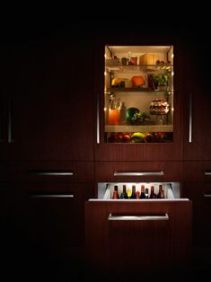 Our modern kitchen design features beautiful refrigerator lighting that displays your food and a pull out drawer for wine and bottled beverages.