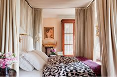Diane von Furstenbergs Paris Apartment. Gold polka dot wallpaper. Neutrals with plum and black accents balance antiques.