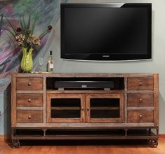 "Urban Gold 76"" TV Stand. Maintains its rustic flavor with a metal base on metal wheels. $935."