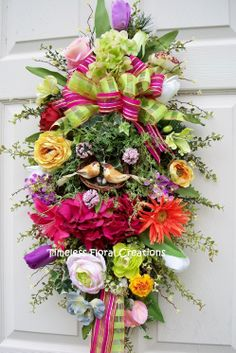 Spring into summer! with this colorful door swag. http://www.timelessfloralcreations.com/ https://www.facebook.com/timelesswreaths