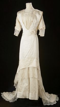 """circa 1910. Jennie Louise Mackinnon's wedding gown shows the influence of Parisian designer Poiret with its slim silhouette and tuinc over dress. The Calgary Herald newspaper described the 1910 wedding and the dress: """" ... ivory satin and chantilly lace, with court train and long tulle veil.... made on the princess lines, with a tunic effect; the overdress faced back with the lace and edged with large pearls."""""""