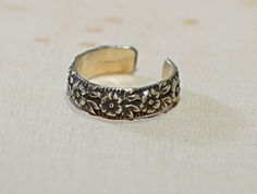 Antiqued with a dark patina for an old fashion appearance, this sterling silver toe ring features a floral pattern with gorgeous contrast to the