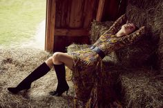 Woman with yellow floral dress and black boots laying on hay bale in a barn - Mark DeLong: Fashion Gallery