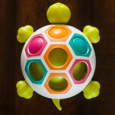 Pop & Slide Shelly and thousands more of the very best toys at Fat Brain Toys. Covering this happy turtle's shell are seven vibrant hexagons in four soothing colors while just beneath the surface are three buttons in teal, orange, and magenta. Push and slide the buttons from slot to slot to match the colors - Giggles erupt when they POP into place!