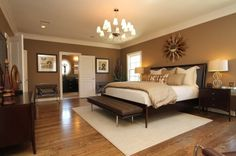 """Master Bedroom - Relaxing in warm neutrals and luxurious bedding, This large Master Bedroom has room for a king size bed, a nice seating area and a media center. this room is kept very subdued using only shades of creme and brown.    3/4"""" x 5"""" oak hardwood planks. Wall color is SW 7525 Tree Branch and trim / ceiling color is SW 6105 Divine White. Chandelier by ET2.  Sunburst mirror by Christopher Guy.  Rug is Ethan Allen.  Bedding is by Home Treasures."""