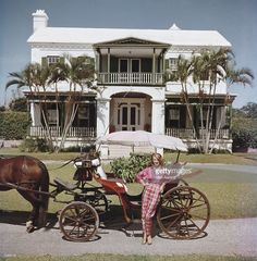 Polly Trott Hornburg in front of her father's typical Bermudian house. She is wearing her own design of Thaibok slacks and shirt for a ride in an open carriage. A Wonderful Time - Slim Aarons A Wonderful Time - Slim Aarons