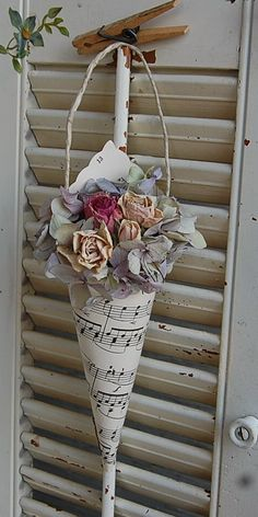 So pretty! Vintage Paper Hymnal Sheet Music Cone with Dried Hydrangea & Roses. $16.00, via Etsy.