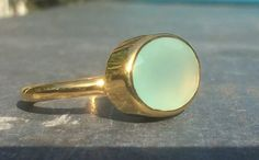 This is a beautiful aqua chalcedony oval stone ring, bezel set in a simple 18 kt gold vermeil band. A very pretty ring that looks great on its own or wear it with one or more of our different shaped gemstone rings to really get noticed! * Gemstone Size: approx. 14 x 10 mm * 18 kt Gold Vermeil (18 kt Gold Plated Sterling Silver) Please see our full collection of rings:- https://www.etsy.com/shop/LavantaBay?section_id=14060292&ref=shopsection_leftnav_4 https://www.etsy.com/shop/LavantaBay?...