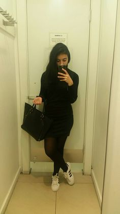 Short black dress with white sneakers, black hand bag and long earings