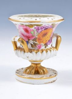 A small Bloor Period Derby porcelain campana vase, 1820-30, partly reticulated, semi-fluted, panoramically painted with flowers, including roses, carnations and primulas, triformed lion-paw feet, on a circular plinth,