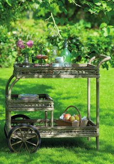 I have an antique wicker tea cart similar to this, only it's brown and it never ventures out of doors.