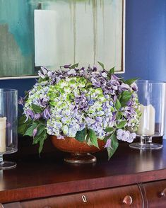 A purple floral arrangement by Kirk Whitfield of K & Co Flowers in a room painted royal blue. The arrangement, which includes sweet peas, hydrangea, and clematis, fills a large bowl set on a dark wood sideboard. An abstract painting, also featuring blue tones, hangs in the background Spring Flower Arrangements, Floral Arrangements, Spring Colors, Spring Flowers, Dark Wood Sideboard, Scented Geranium, Vinyl Wallpaper, Blue Accents, Room Paint
