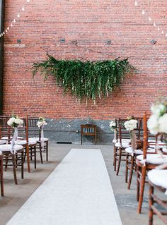 Greenery and bright flower backdrop hanging from wall behind top of ceremony. candles along aisle. greenery and flower bushels hanging from edge of chairs or strung along aisle floor.