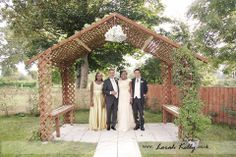 The bride and groom with the wedding party under a canopy. Photography by Lorah Kelly | www.lorahkelly.co.uk