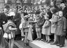Op het plein voor het Paleis op de Dam kijken Koningin Juliana, prinses Margriet en prinses Marijke toe, hoe een zwart pietje lekkers uitdeelt aan kinderen te Amsterdam, Nederland 22 november 1952.