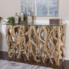 Bring some natural beauty into your beach house with this gorgeous Driftwood Console Table. It's teak base and glass top will lend some serious style to your home.