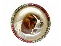Spaniel Crystal, Ruby  Diamond Brooch Edwardian (1901-1914) Item No. 929A  A beatuifully worked reverse intaglio crystal brooch from around 1910.  A very detailed spaniel's head with a border of old rose-cut Diamonds and square-cut Rubies.  Set in 18ct Gold on a Mother of Pearl base.  In excellent condition, a rare and stunnng piece. £3,950.00