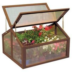 Wood-framed greenhouse with a hinged lid and adjustable locking supports.  Product: GreenhouseConstruction Material: Polycarbonate and woodColor: Brown and clearFeatures: Hinged lid with adjustable locking supportsDimensions: 23 H x 31 W x 35 D