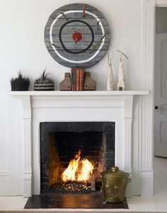 The owner throws foreign coins he brings back from his world travels in the fireplace. The bull's-eye is by artist Michael Ives, white sculptures are by Jean-Paul van Lith, and horsehair hats are from Mali. Rustic Contemporary, White Space, California Homes, White Houses, Rustic Chic, Rustic Loft, Decoration, Living Spaces, Kid Spaces