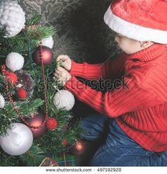 Portrait of asian boy decorating Christmas tree, dressed Santa hat. Family decorating a Cristmas tree