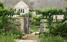 17th century farmhouse in Devon - Over time entrances had been moved and the impact of the space was lost. The main route into the house was re-established, forming an outer court by planting ancient espalier pears & commissioning a bespoke oak gate, inspired by wooden spindles from within the house, as the main entrance through the walls. The front court itself is now filled with fragrant lavender, violas, geraniums, and mature yew topiaries.  - Arne Maynard Garden Design