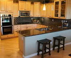 Love the black backsplash and countertops with the wooden cabinets!