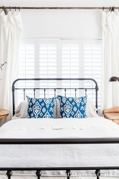 White linen duvet and bold blue pillows... Looking to add a seasonal touch to your bedroom? Don't miss these incredibly simple master bedroom decorating ideas for spring! #springdecor #springbedroom #nightstand #modernfarmhouse