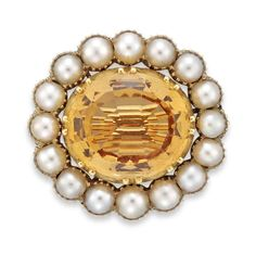 A Georgian topaz and pearl cluster brooch, the oval faceted topaz estimated to weigh 5.20 carats cut down-set inbetween an half pearl cluster surround all to a yellow gold mount, with brooch fitting, circa 1800 Gross weight 4.6 grams