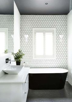 revêtement mural avec carreayux hexagone en blanc avec baignoire noire