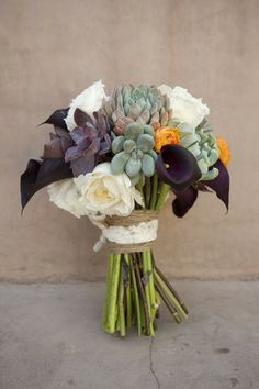 This desert botanical bouquet combines rich purples and pops of orange with neutral succulents!