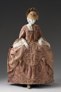 The fashionable vogue of wearing a robe a la française dressed a la Polonaise displays the overskirt of the dress tied at the sides using interior cords and/or ribbons or buttons to form three large poufs. English Spitalfields silk brocade is worked in a rose-tone with cream stripes with floral motifs scattered across the ground. Colorful small flowers and white blossoms ornament the design of the fabric. This sumptuous floral patterned silk dress has been trimmed with white fly fringe.
