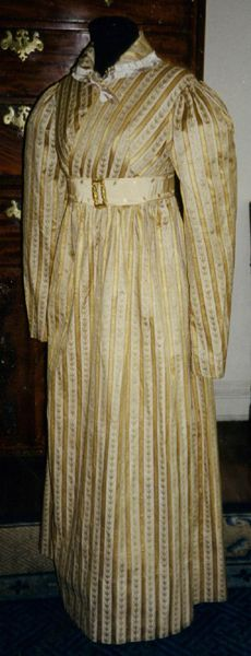 Date Made: 1816  Description:  Dress; late Empire style, striped beige cotton with woven green and pink sprigs alternating with gold satin stripe, worn as a wedding dress.