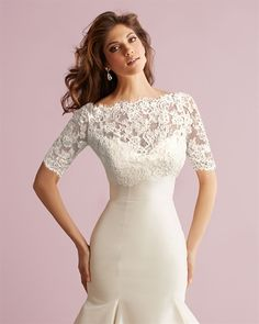 This cropped lace bolero features a bateau neckline and three quarter length sleeves.